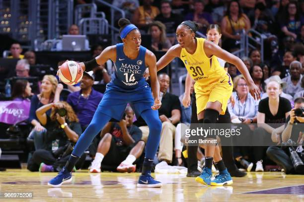Temi Fagbenle of the Minnesota Lynx handles the ball against Nneka Ogwumike of the Los Angeles Sparks during a WNBA basketball game at Staples Center...