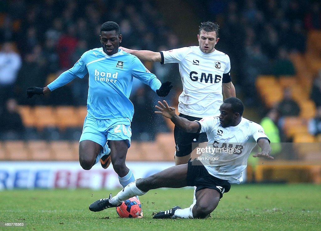 Temitope Obadeyi of Plymouth Argyle holds off Doug Loft and Anthony Griffith of Port Vale during the Budweiser FA Cup third round match between Port Vale and Plymouth Argyle at Vale Park on January 5, 2014 in Burslem, England.