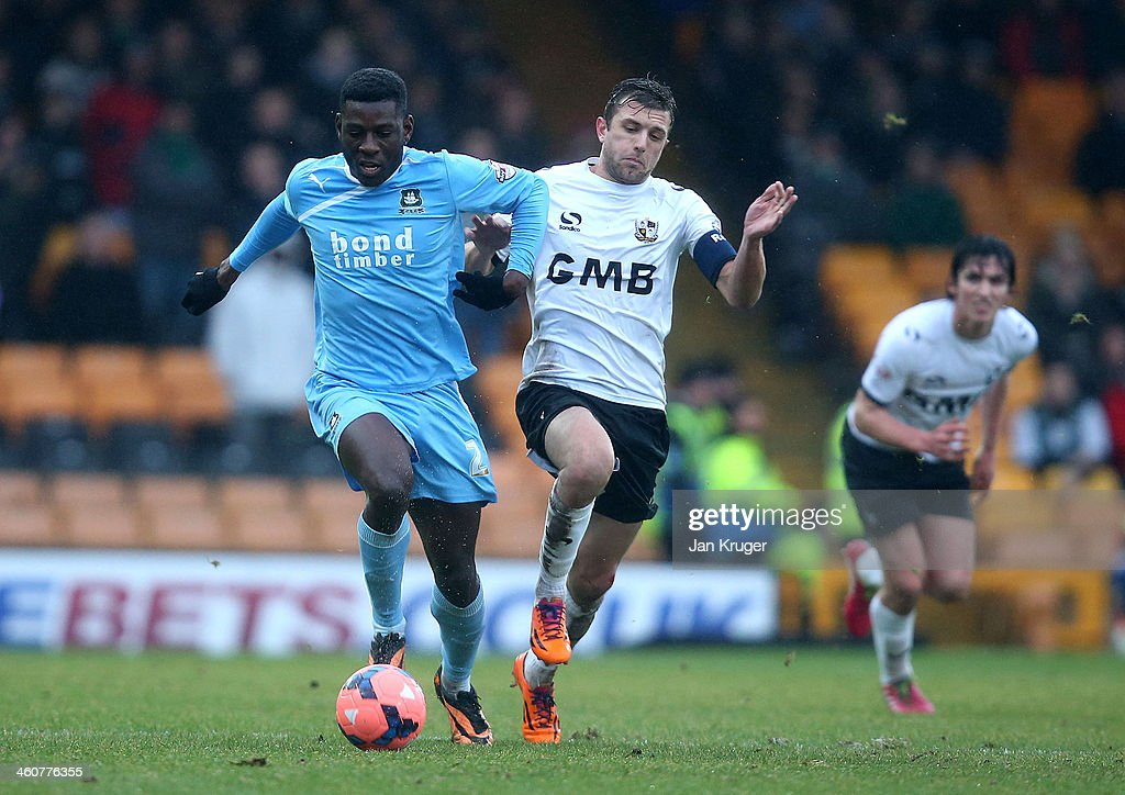 Temitope Obadeyi of Plymouth Argyle holds off Doug Loft of Port Vale during the Budweiser FA Cup third round match between Port Vale and Plymouth Argyle at Vale Park on January 5, 2014 in Burslem, England.