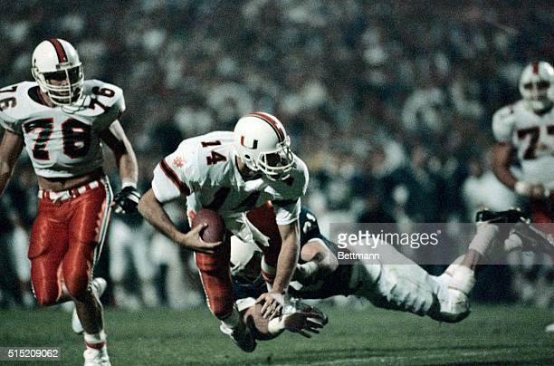 Miami quarterback Vinnie Testaverde is brought down by Penn State outside linebacker Shane Conlan for a loss of yardage in third quarter action 1/2