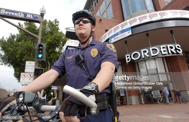 Tempe, AZ police officer Dan Wong keeps an eye out for suspicious activity at the corner of Seventh St. And Mill Ave. In Downtown Tempe, AZ. Borders,...