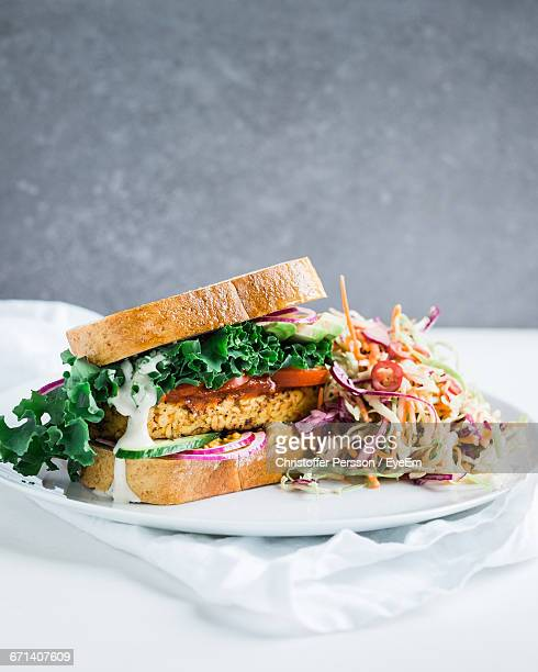 tempeh and kale sandwich with chili coleslaw on table - テンペ ストックフォトと画像