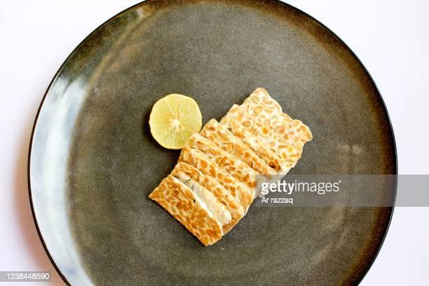 tempeh slices on a black plate - テンペ ストックフォトと画像