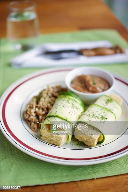Tempeh wrapped in zucchini, with a rhubarb mustard sauce and spelt on plate