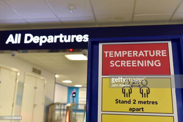 "Temperature Screening"" sign and fever screening thermographic cameras which can measure higher body temperature at the departure gate as London..."