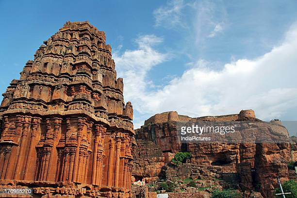 A temple built in red sandstone at Badami along with a spectacular view of the rocky hills in the background Bagalkot Karnataka India