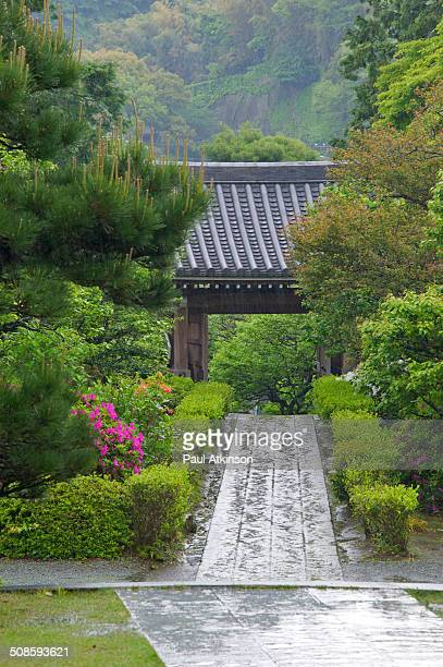 A temple gate in Kamakura an historic Japanese town famous for its temples Lush vegetation from the spring rains