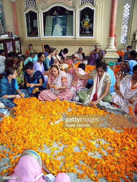 Temple inside women making yellow offering flower beads for the pilgrims.