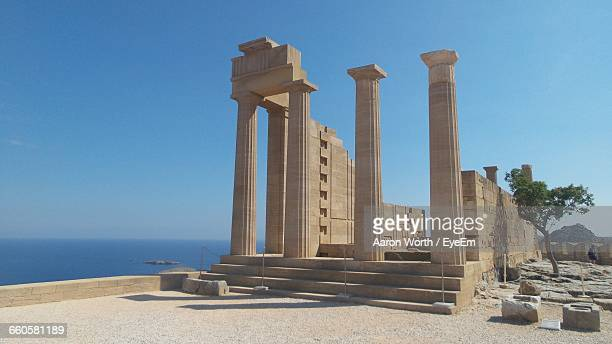 temple of athena by sea against clear sky - lindos stock photos and pictures