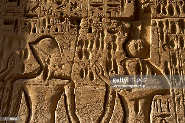 Temple of Ramses III, The pharaoh Ramses III before the war-god Monthu, with falcon-headed, solar disk and crown with two feathers, New Kingdom, ,...
