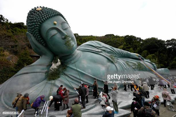 Temple parishioners clean up the Reclining Buddha with bamboo branches at Nanzoin Temple on December 26 2017 in Sasaguri Fukuoka Japan Some 200 monks...