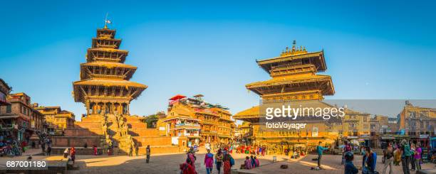 Temples and tourists illuminated by warm sunset light Kathmandu Nepal