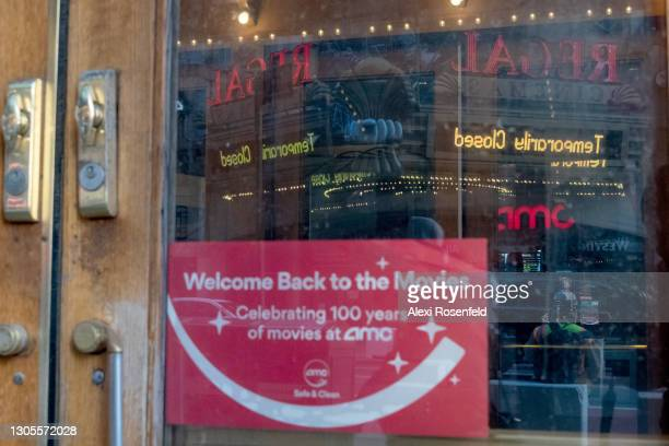 """Temporarily closed"""" sign at Regal cinema is reflected off a door at AMC Empire 25 where a """"welcome back to the movies"""" sign is displayed in Times..."""
