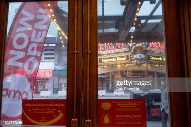 """Temporarily Closed"""" sign is displayed at a Regal Cinemas, framed by a """"now open"""" banner and COVID-19 related signs on a door at AMC Empire 25 in..."""