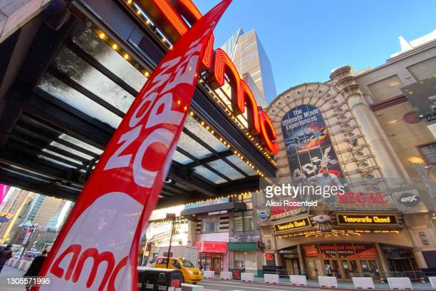 """Temporarily Closed"""" sign is displayed on the marquee of the Regal Cinemas across the street from a """"now open"""" banner at AMC Empire 25 in Times Square..."""
