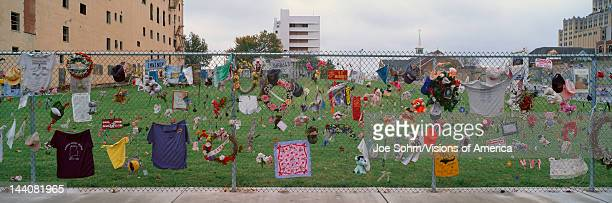 Temporary Memorial for 1995 Oklahoma City Bombing with flags pictures and personal notes on fence