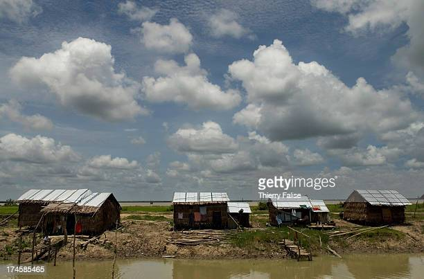 A temporary settlement of houses made of straw and tarpaulin for survivors of cyclone Nargis lies along a canal According to official figures the...