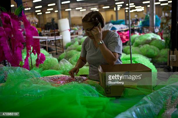 A temporary worker talks on a mobile phone while making a costume for Brazil's carnival celebration at the Mangueira samba school building in Rio de...