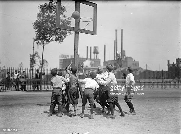 Ten boys battle for the rebound after a shot has been taken during a basketball game on an outdoor playground New York ca1920s