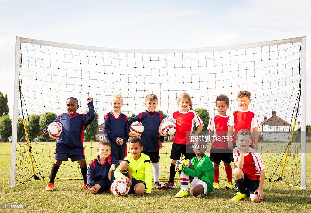 Ten children standing in football goal : Foto de stock