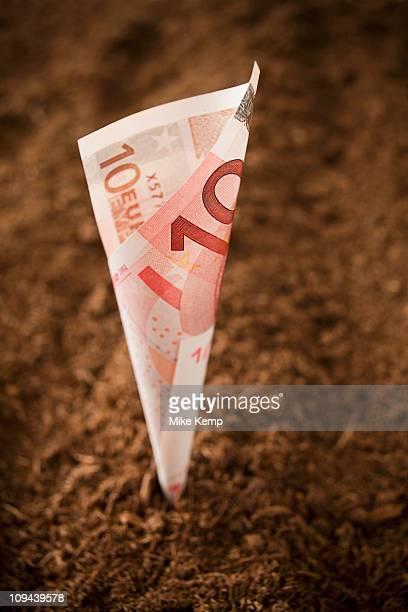 Ten euros Banknote growing from dirt, studio shot