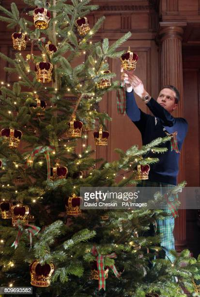 A ten foot tall Christmas tree in the Great Gallery is decorated by staff member Andrew Grant at the Palace of Holyroodhouse Edinburgh