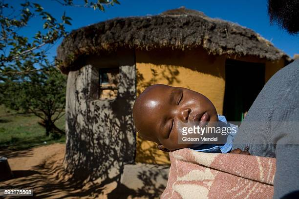 Ten month old baby Mpho who is HIV positive sleeps on the back of his mother Mathato Notsi while she sweeps her yard He had just received the morning...