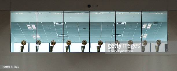 Ten National Basketball Association Larry O'Brien championship trophies are placed above the basket ball court of the new Los Angeles Lakers training...