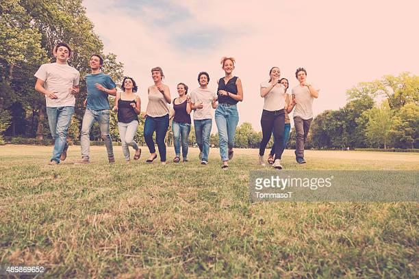 dieci adolescenti corre su un campo verde al parco - tempo libero foto e immagini stock