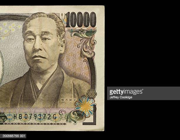 Ten thousand Yen note against black background, close-up