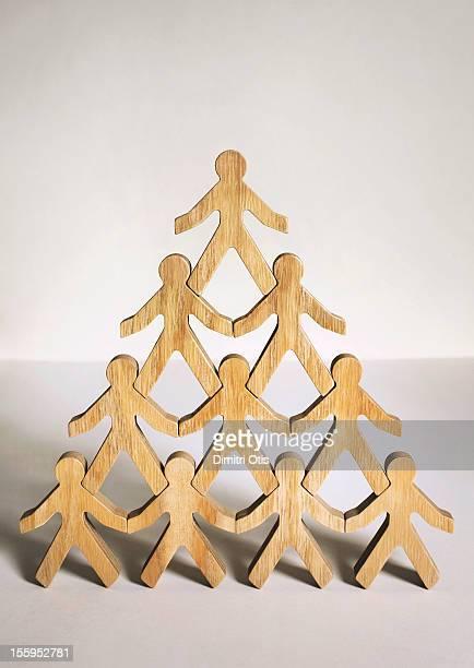 Ten wooden model men standing in pyramid formation