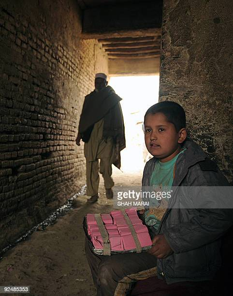 Ten year old Afghan street vendor Aziza Hamad waits for customers in Kabul on October 27, 2009. Afghanistan's presidential rivals are reigniting...