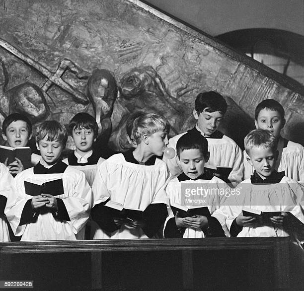 Ten year old choirboy Ian Stacey of Bethnal Green tries to break the concentration of his friend by blowing bubbles with his bubble gum during choir...