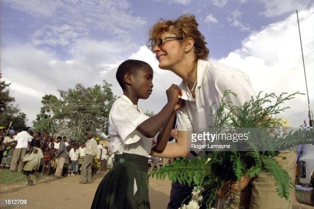A ten year old girl Beatrice Mshaka pins an AIDS ribbon on UNICEF's Goodwill Ambassador Susan Sarandon May 2000 after presenting her with flowers...