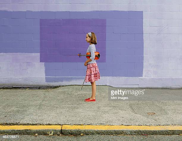 A ten year old girl holding a violin under her arm and a bow in her hand. Against a purple background.