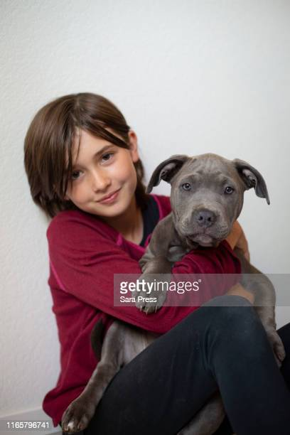 ten year old girl with 3 month old puppy - gender fluid stock pictures, royalty-free photos & images