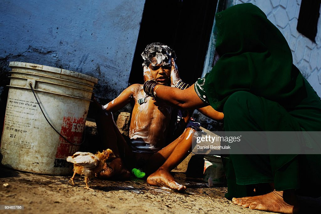 Ten year old Nawab Mian, suffering from mental illness related to the 1984 disaster, receives his morning wash near the site of the deserted Union Carbide factory on November 28, 2009 in Bhopal, India. Twenty-five years after an explosion causing a mass gas leak, in the Union Carbide factory in Bhopal, killed at least eight thousand people, toxic material from the 'biggest industrial disaster in history' continues to affect Bhopalis. A new generation is growing up sick, disabled and struggling for justice. The effects of the disaster on the health of generations to come, both through genetics, transferred from gas victims to their children and through the ongoing severe contamination, caused by the Union Carbide factory, has only started to develop visible forms recently.