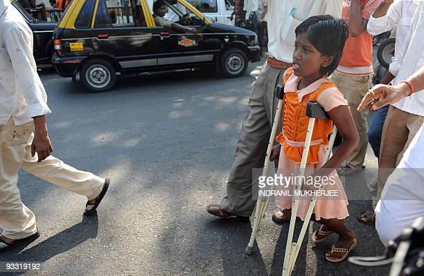 Ten yearold Devika Rotawan a survivor of the November 2008 militant attacks walks with the help of crutches after a protest against the lone...