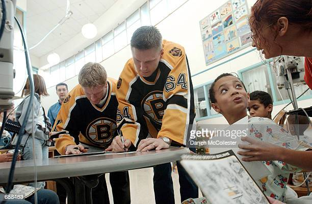 Ten yearold Trevor Wesley of Lynn MA gets an autograph December 19 2001 from Boston Bruins players Jarno Kultanen and PJ Axelsson at the Childrens...
