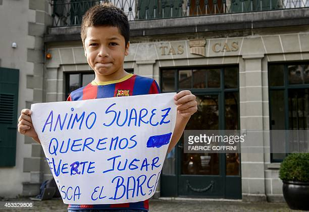 Ten years old Carlo poses with a placard reading 'Come on Suarez we want to see you playing at Barca' in front of the Court of Arbitration for Sport...