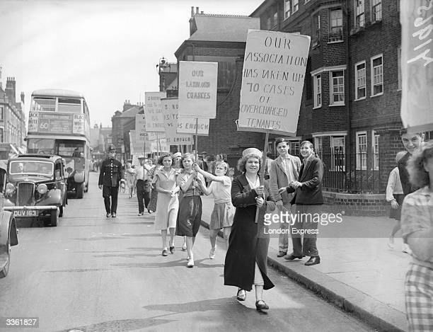 Tenants from Quinns Buildings in Bethnal Green London march through the streets carrying banners during a rent strike protesting over housing...