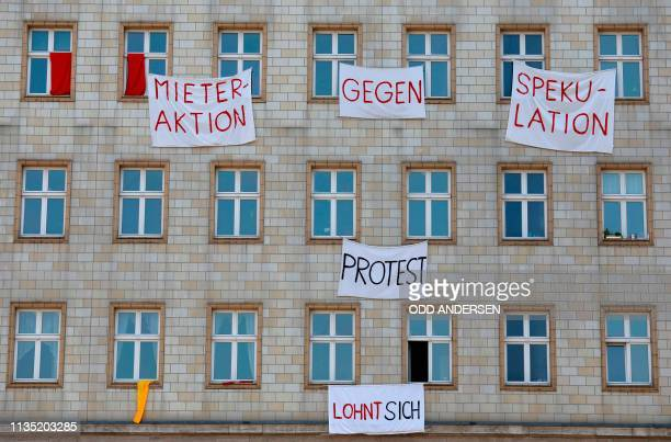 TOPSHOT Tenants protest against the sale of their flats against gentrification and rising rents by hanging out banners out of their windows in...