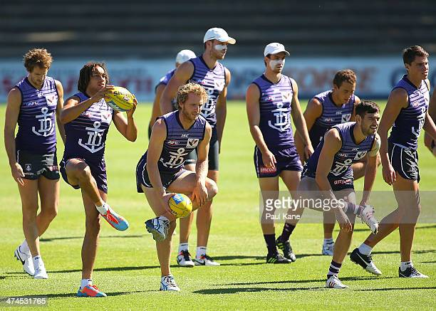 Tendai Mzungu and David Mundy warm up during a Fremantle Dockers AFL training session at Fremantle Oval on February 24 2014 in Fremantle Australia