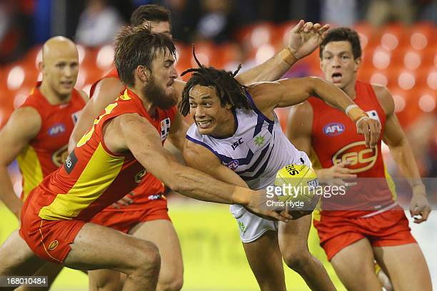 Tendal Mzungu of the Dockers is tackled by Charlie Dixon of the Suns during the round six AFL match between the Gold Coast Suns and the Fremantle...