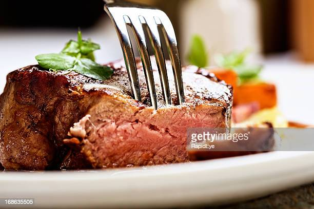 Tender and juicy, a fork pierces grilled beef fillet