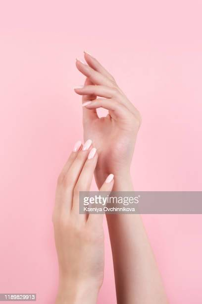 tender hands with perfect blue and pink manicure on trendy pastel pink background. place for text. - 清らか ストックフォトと画像