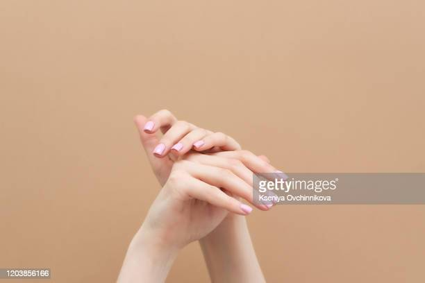 tender hands with pink manicure on trendy pastel pink background. place for text. - woman flashing stock pictures, royalty-free photos & images