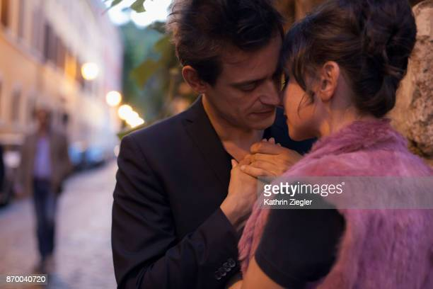 A tender moment between a couple at a street corner, Rome, Italy