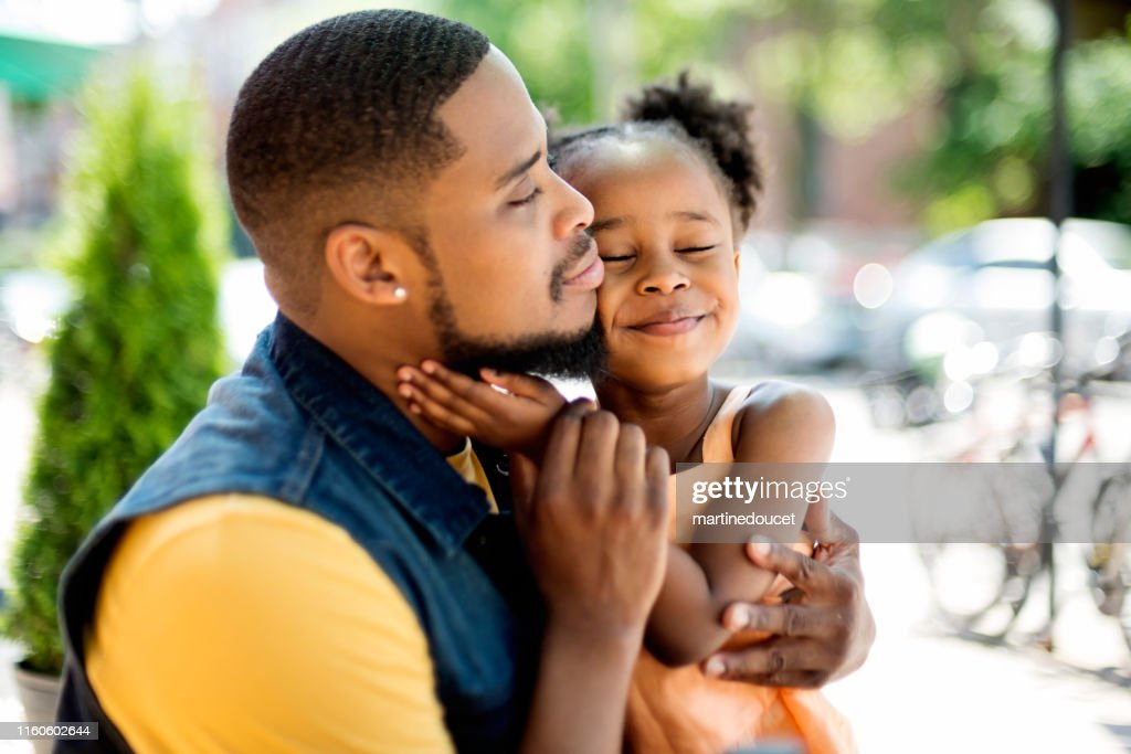 Tender moment between father and daughter on summer terrace. : Stock Photo