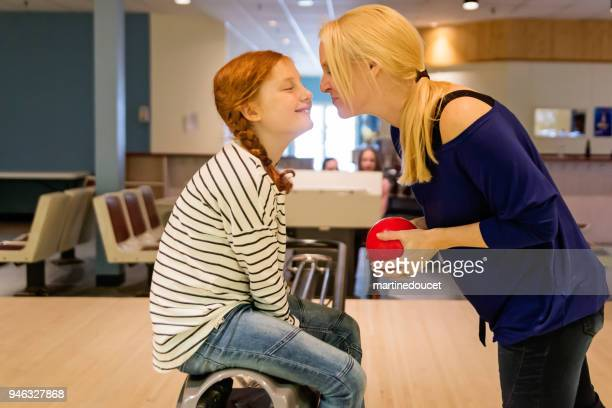 Tender moment between mother and daughter playing bowling.